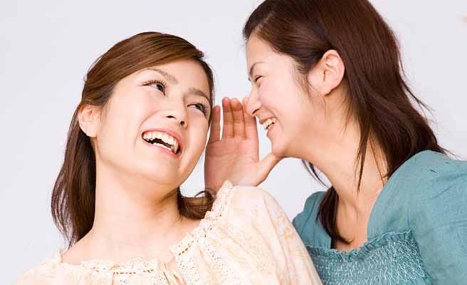 耳打ちする女性と笑顔で聞く女性
