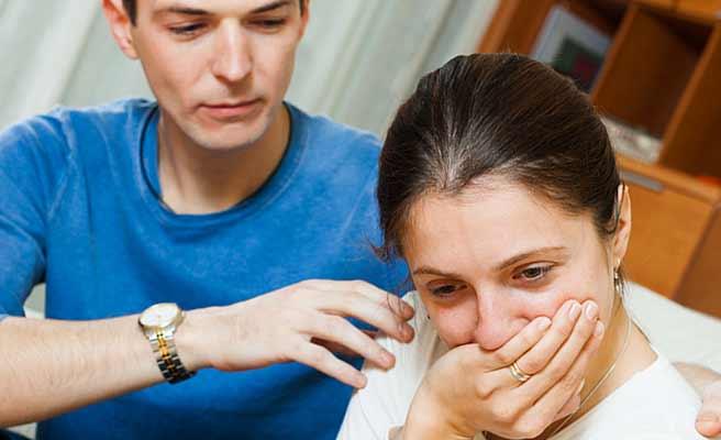 泣きそうな女性の肩に手をのせて困惑する男性