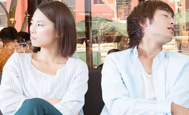 不機嫌な表情の女性と隣で居眠りする彼氏