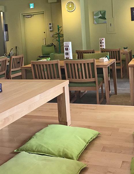 ふんわりした色合いのグリーンに木製のテーブルと椅子がとても優しく感じる店内。