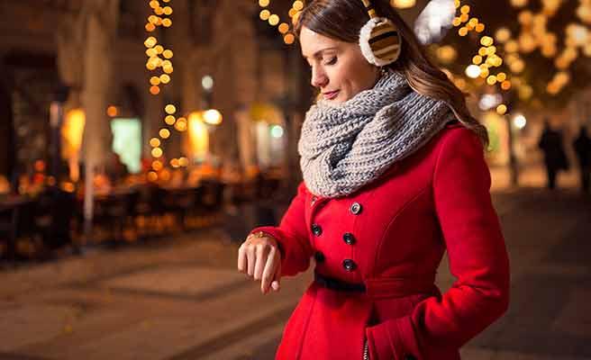 赤いコートを着て腕時計を見る女性