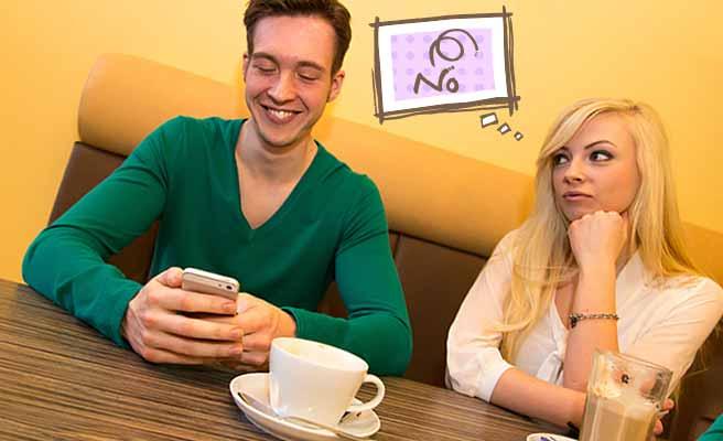 昼デートでスマホに夢中の彼氏と不満な女性