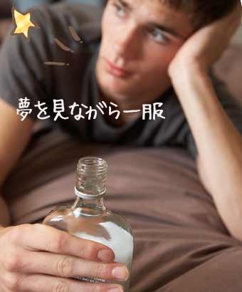 ベッドに寝そべりながらお酒を飲む男性