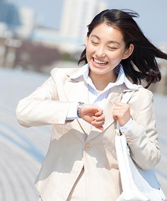 腕時計を見ながら笑顔で歩く女性