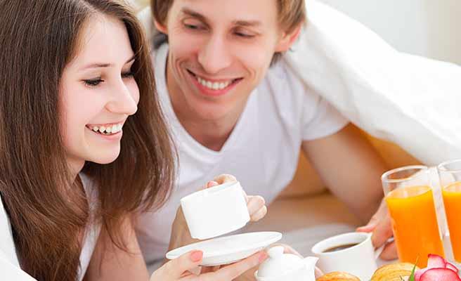 ベッドの上で一緒にコーヒーを飲むカップル