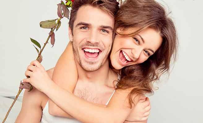 バラ一輪を持って彼氏に抱きつく女性