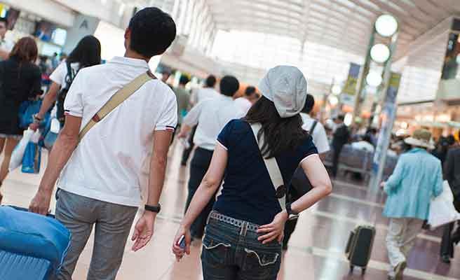 空港のロビーを並んで歩くカップル