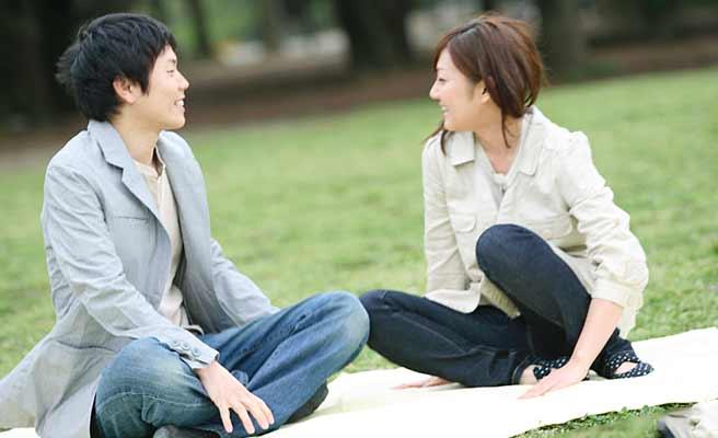 公園の芝生の上で語り合うカップル