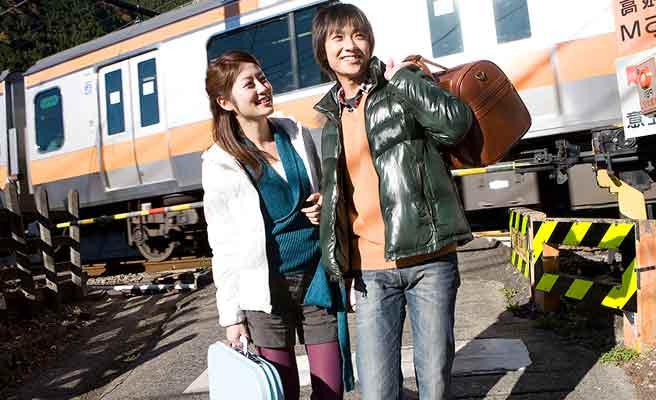 電車の前に立つカップル