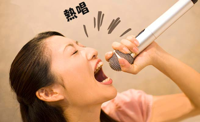 一人カラオケで熱唱する女性