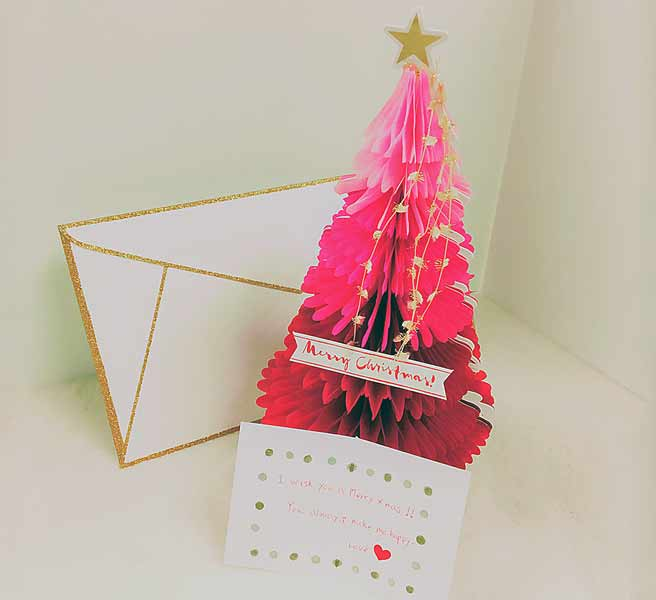 赤いクリスマスツリーの前に立つカード