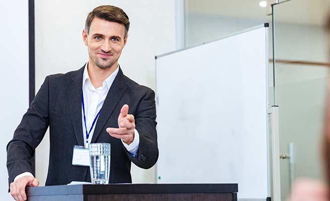 演壇で聴き手を指さすエリート男性