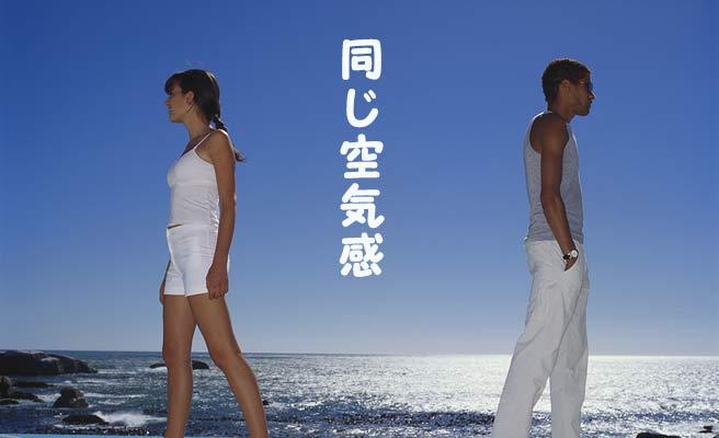 海岸で背中を向けて立つ男女