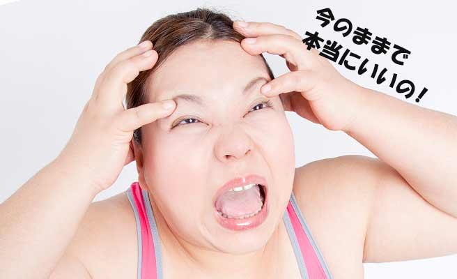 肥満の女性が頭を抱えて悩んでいる