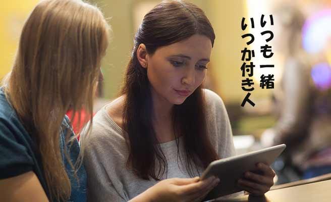一緒にタブレットを見る女性二人組