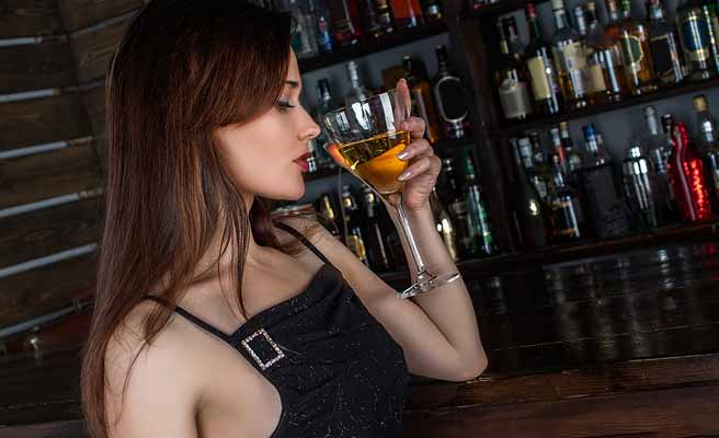 バーでワイングラスを傾ける女性