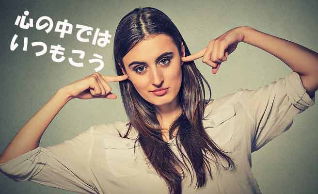 指で両耳を塞ぐ女性