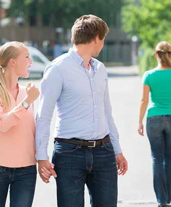 ガールフレンドを手をつなぎながら他の女性を見つめる男性