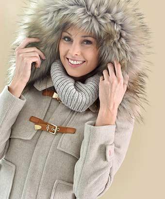 ファー付きのフードがついた上品なコートを着てる女性