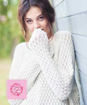 レースのセーターを着て袖で手をかくす女性