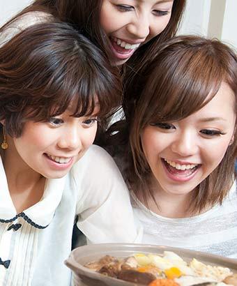 鍋を囲んで笑顔の女性
