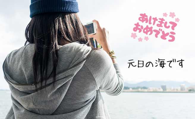 港の風景を写メに撮る女性