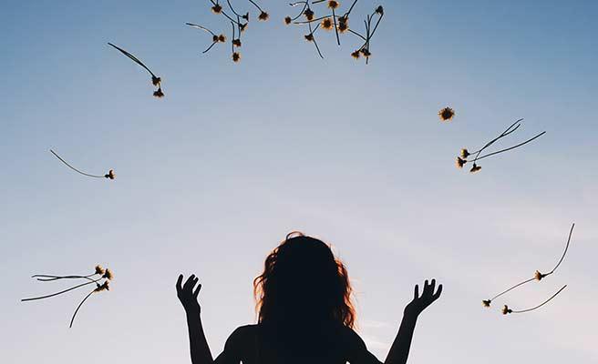 中空に花を放り投げる女性