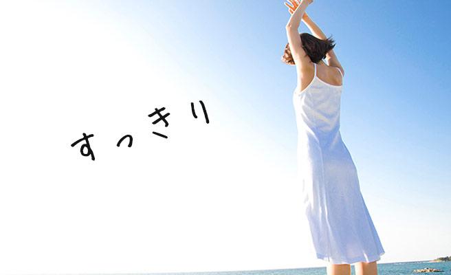 青空に向かって背筋を伸ばす女性