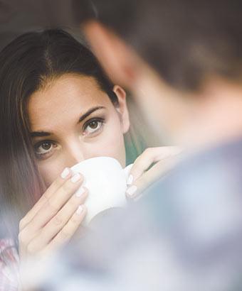 彼とお茶しながら彼を見つめる女性