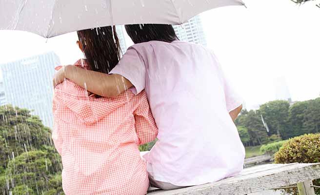 公園のベンチに座る相合い傘のカップル