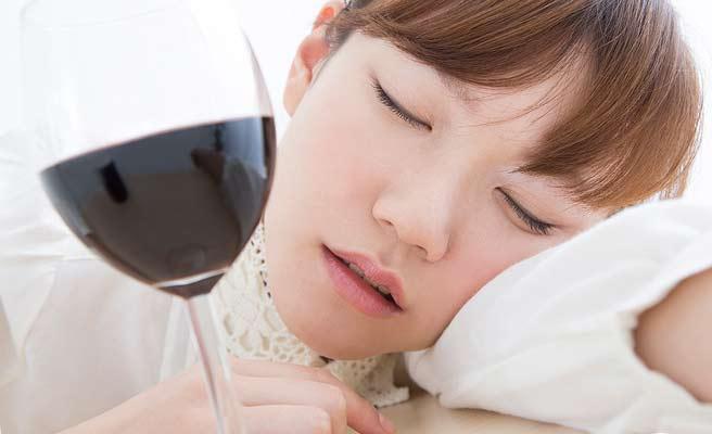 ワイングラスの前で酔いつぶれる女性