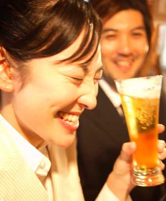 ビールを飲みながら表情に出る女性と笑う男性