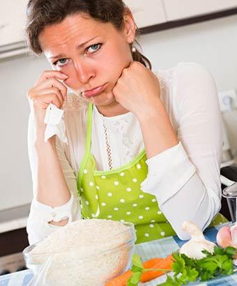 台所で悲しみに暮れる女性