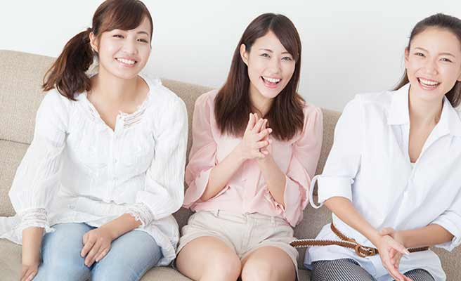 女性3人が並んで腰かけている