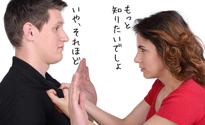 男性に詰め寄る女性とお手上げポーズの男性