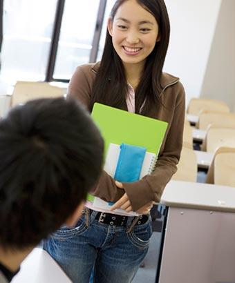 男子学生の前で笑顔で立つ女子学生