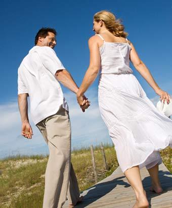 手を繋いで歩道を歩いていくカップル
