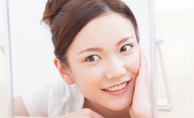 鏡に自分の笑顔を映す女性