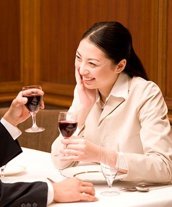 レストランで向い合ってワインを飲む男女