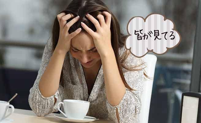 カフェテラスで頭を抱えて泣く女性