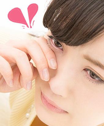 涙を指で拭う女性