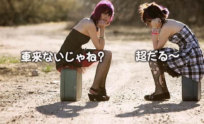 田舎の砂利道で車を待つ女性二人
