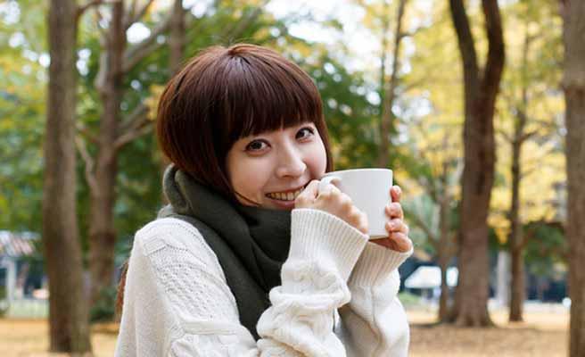 マフラーとニット長袖の女性がコーヒーを飲む