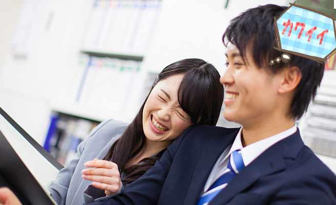 職場で同僚男性の肩にもたれて笑う女性