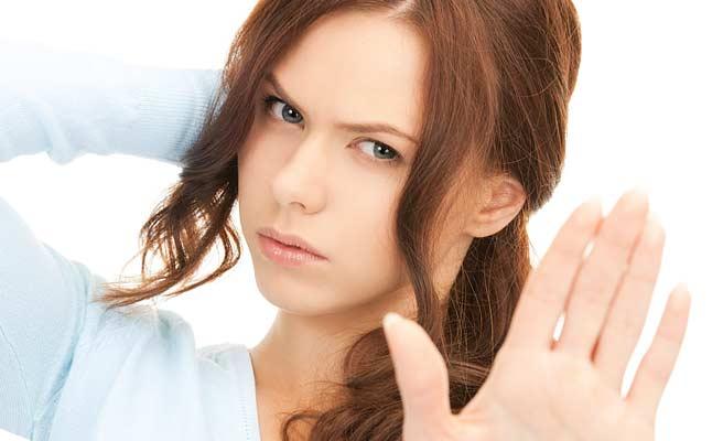 不愛想な女性が手で制止する