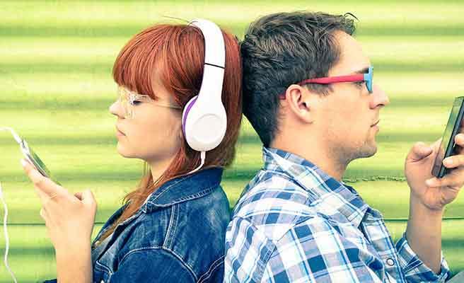 彼氏と背中合わせに座ってヘッドホンで音楽を聴く女性