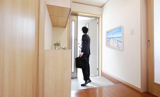 写真を掛けた玄関から出勤する男性