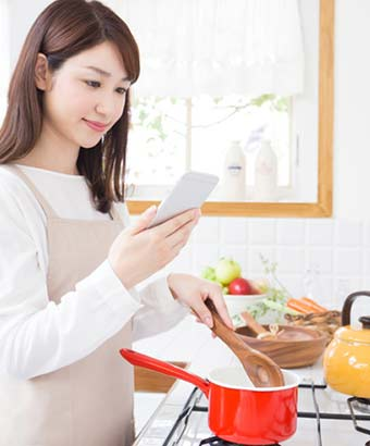 スマホで調べながら調理する女性