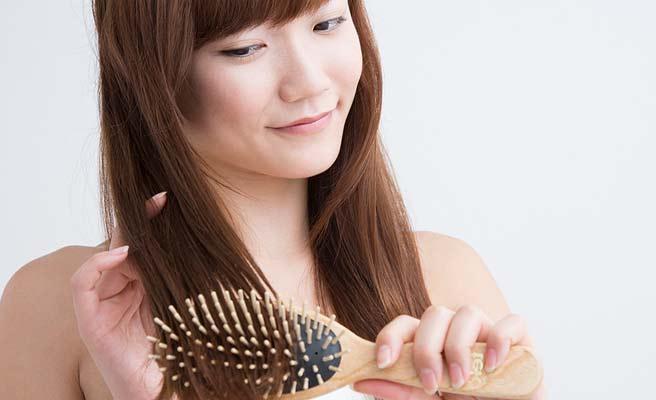 髪にブラシをかける女性