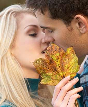 枯葉でキスを隠す女性